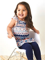 A toddler girl is seated, wearing a print top and blue leggings. Shop Toddler Girls.