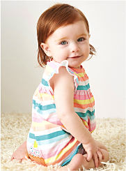 A baby girl is wearing a striped outfit with ruffle sleeves. Shop Baby Girls.