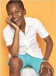 A boy wearing a white button-front shirt and turquoise shorts. Shop Boys 8-20.