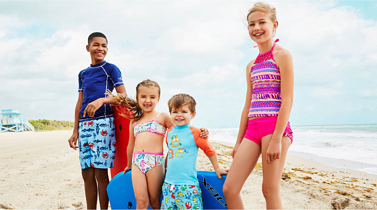 Two boys and two girls standing on a beach, wearing various styles of swimwear.