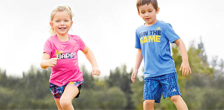 A girl and a boy running, wearing graphic tees and print shorts.