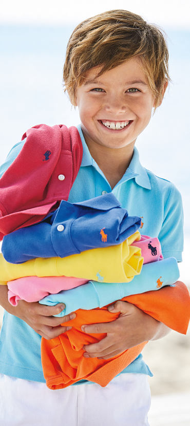 A boy wearing a blue Polo Ralph Lauren shirt, holding an assortment of other polos.