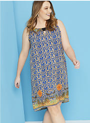 A woman wearing a sleeveless printed dress. Shop dresses.