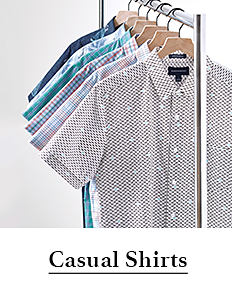 An assortment of men's short sleeved button front shirts on hangers in a variety of colors & prints. Shop casual shirts.