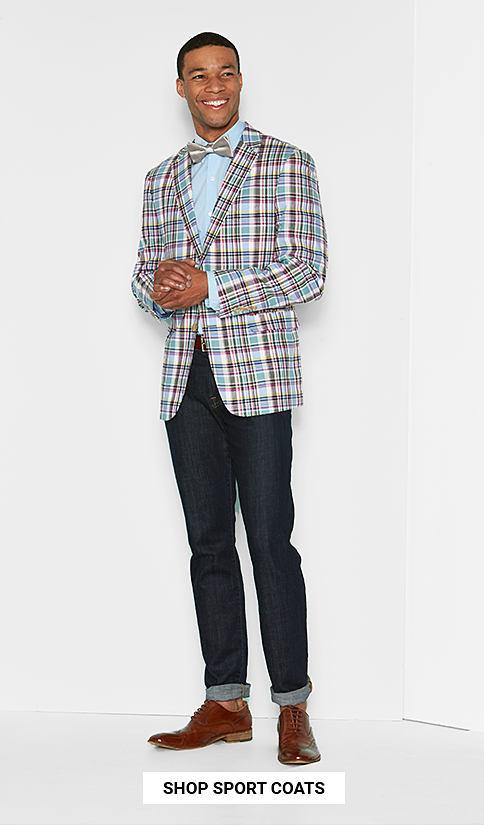 A man wearing a multi colored plaid sport coat, a light blue dress shirt, a plaid bow tie, blue jeans & brown leather shoes. Shop sport coats.