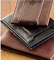 Three leather wallets on a wooden table.