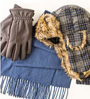 A pair of brown leather gloves, a blue scarf, and a plaid hat with ear flaps that is lined with faux fur on the inside.
