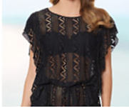 A woman wearing a black swimsuit cover-up top with cutout pattern details.