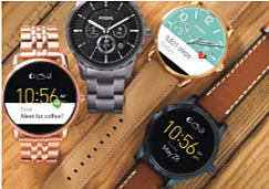 Four smart watches laying on a wooden surface.