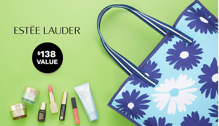 An assortment of Estee Lauder women's beauty products and a blue floral tote.