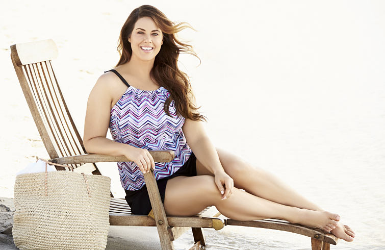 A woman wearing a plus size printed swimsuit on the beach.