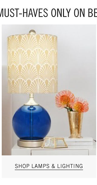 A blue glass lamp with a beige patterned print lampshade. Shop lamps & lighting.
