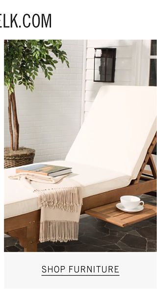 A wooden chaise lounge with a white seat cushion next to a little wooden table. Shop furniture.