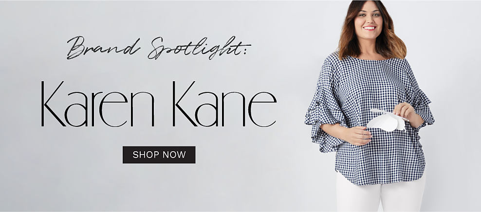 A woman wearing a black & white houndstooth print long sleeved top & white pants. Brand Spotlight. Karen Kane. Shop now.
