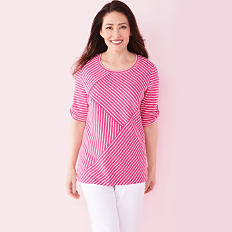 A woman wearing a pink short sleeved top & white pants. Km Rogers. Shop now.
