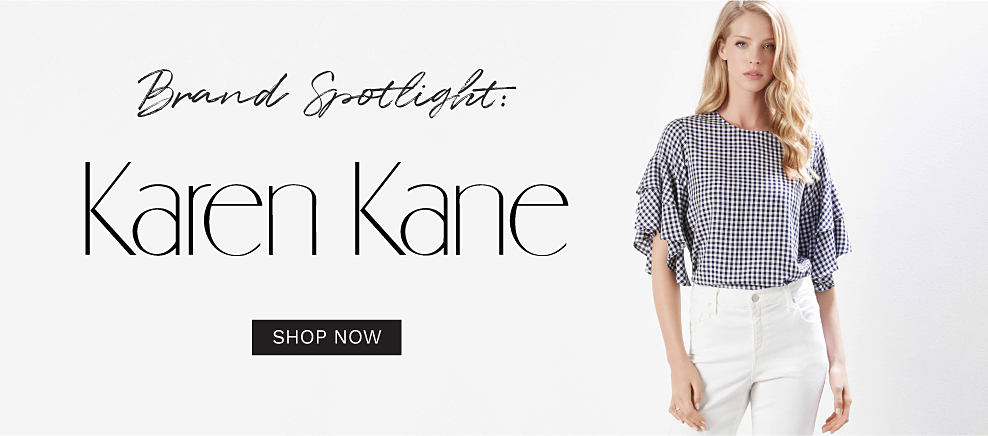 A woman wearing a black & white houndstooth print short sleeved top & white pants. Brand Spotlight. Karen Kane. Shop now.