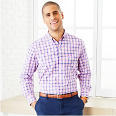 A man wearing a blue, red & white plaid long sleeved button front shirt & blue pants.