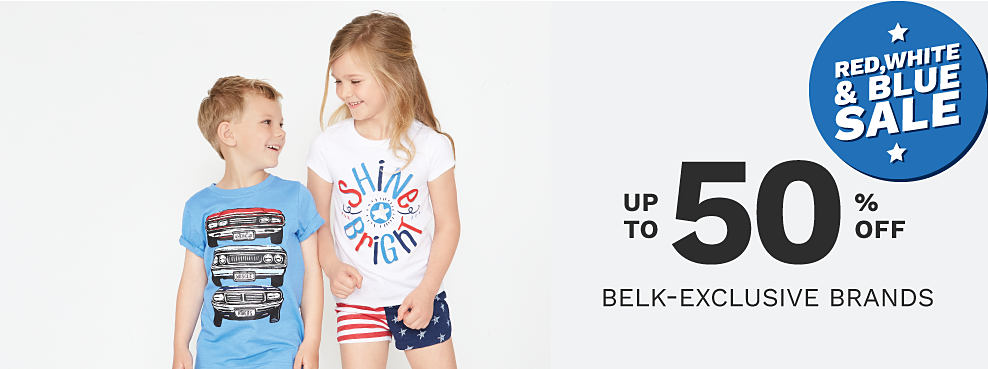 A boy wearing a light blue T shirt with a multi colored convertible front graphic & gray shorts standing next to a girl wearing a red, white & blue Shine Brightly graphic tee & red, white & blue stars & stripes print shorts. Red, White & Blue Sale. Up to 50% off Belk exclusive brands.