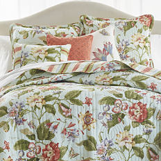 A bed made with a floral print quilt & matching pillows. Shop quilts.