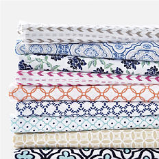 A stack of folded bed sheets in a variety of colors & patterns. Shop sheets.