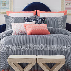 A bed made with a grey printed comforter and grey and coral accent pillows. Shop comforters.