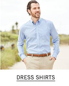 e69144392a1 A man wearing a light blue dress shirt & beige pants. Shop dress shirts.