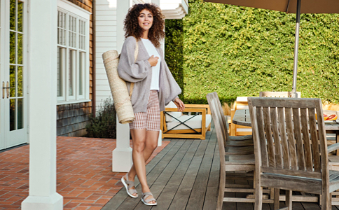 A woman standing on an outdoor patio next to a table and chairs with a large umbrella. She's wearing a white top layered with a tan open front cardigan, red and white striped shorts and tan sandals with straps and carrying a rolled yoga mat with a strap.