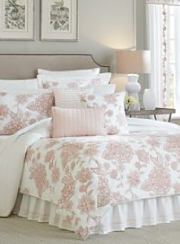 Pink and white floral bedding on a bed. Shop designer bedding.