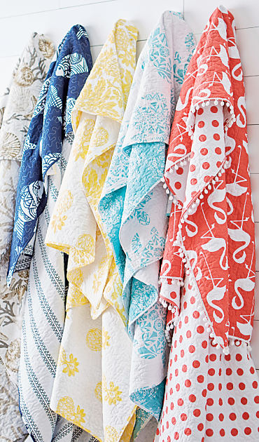 A row of red, yellow, blue and white patterned quilts hanging from hooks. Shop bedding.