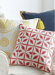 Patterned red and yellow throw pillows on a chair. Shop pillows.
