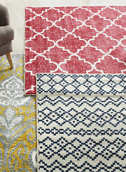 A collection of patterned area rugs in red, yellow and blue. Shop rugs.