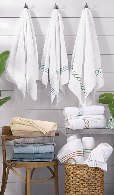 Bath towels hanging from hooks, stacked in a chair and piled in a basket. Shop bath.