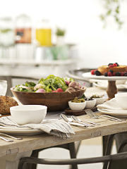 A dinner table set with food, plates. bowls and silverware. Shop dining.