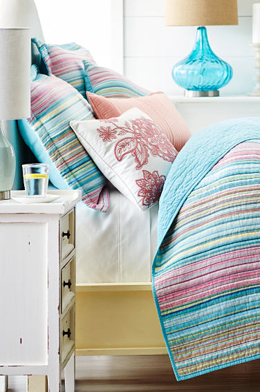 A bed made with a pastel print quilt and pastel print pillows. Shop bedding.
