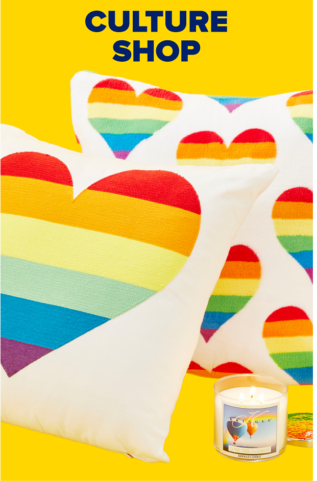 Two decorative pillows featuring rainbow colored hearts, and a small candle featuring a rainbow and hot air balloon. Culture Shop.
