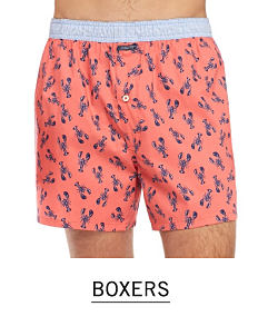 A man wearing coral boxer shorts with a navy lobster print & gray waist band. Shop boxers.