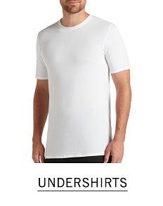 A man wearing a white T shirt & navy pants. Shop undershirts.