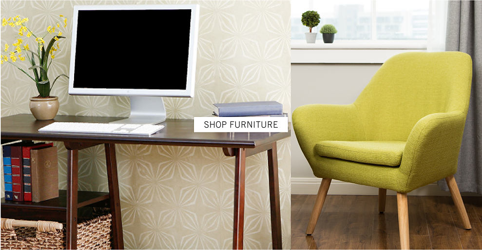 A computer on a table, a small plant, and a green chair shop furniture.