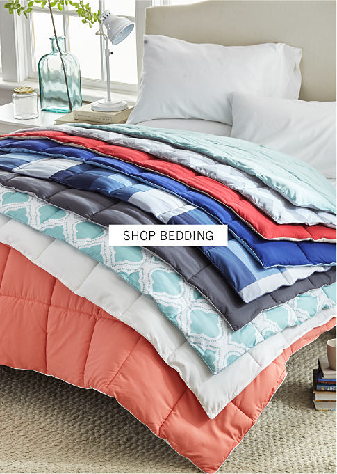 A bed with a stack of comforters in a variety of prints and colors. Shop bedding