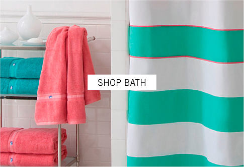 A stripe shower curtain and a rack with folded pink and green towels. Shop bath.