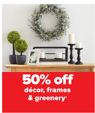 A table set with artificial plants, photos, and candles, with a green wreath above it. Up to 60% off decor, frames and greenery.