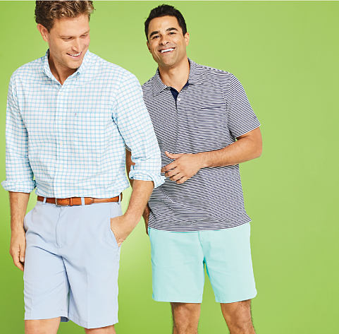 Two men wearing shorts and summer shirts.