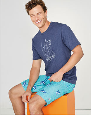 A man wearing a light blue swimsuit and t-shirt.