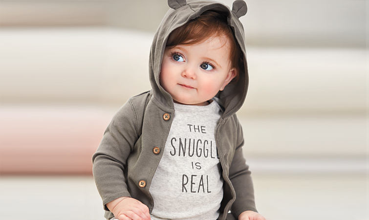 A baby is wearing a Carter's graphic tee and a hoodie with bear ears.