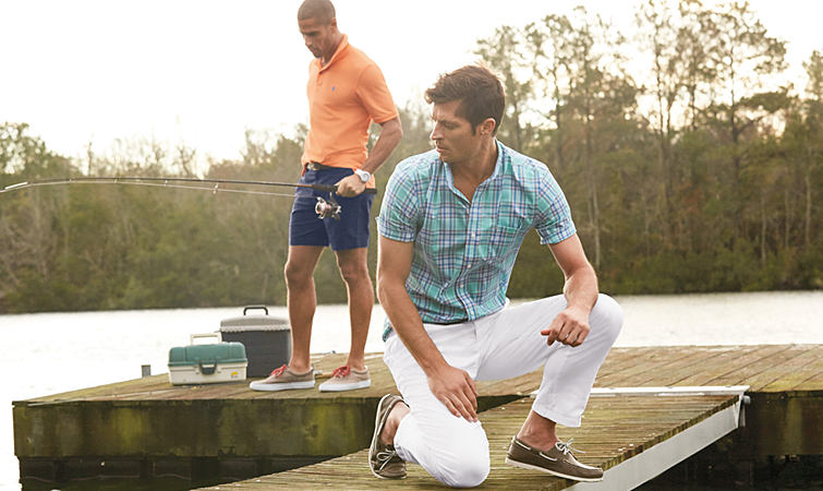 Two men standing on a dock fishing, wearing casual stretch comfort apparel.