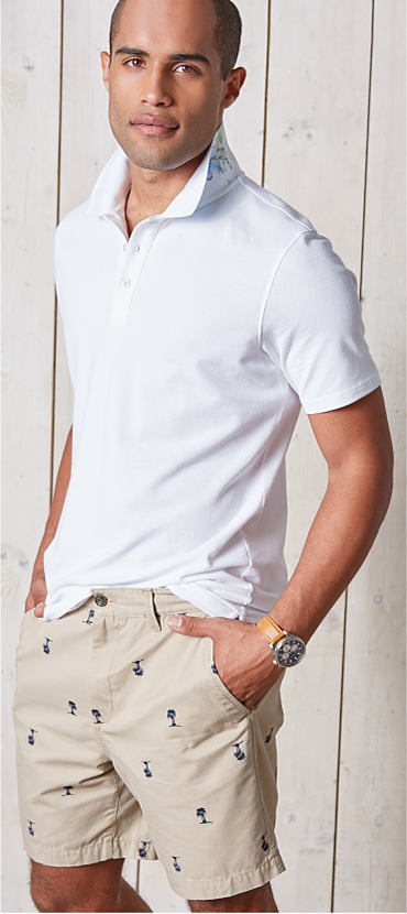 A man wearing a Crown and Ivy shirt and shorts. Shop Belk-exclusive brands.