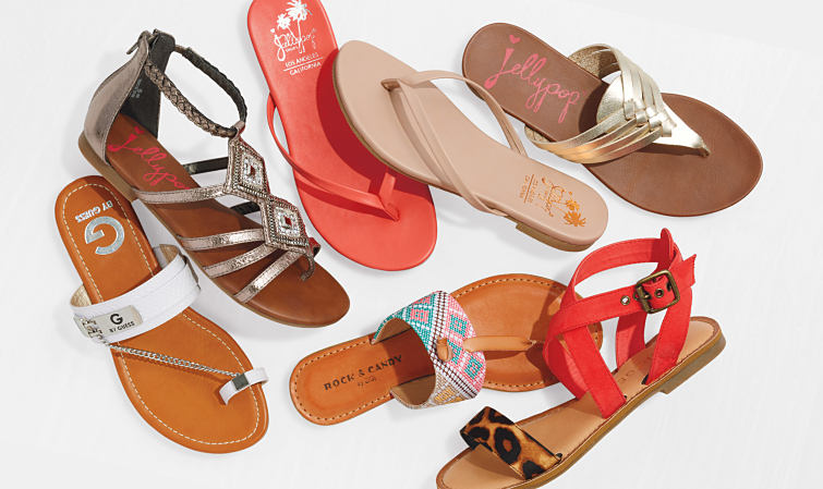 An assortment of women's strappy sandals and slides.