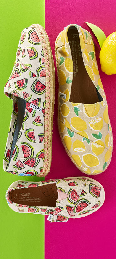 Two pairs of TOMS casual shoes, one with a watermelon print and the other with a lemon print.