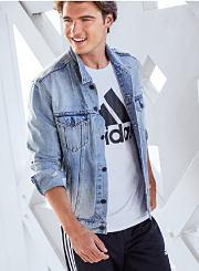 A young man wearing a denim jacket over an Adidas T-shirt. Shop activewear.