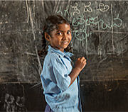 A smiling young child in front of a chalkboard.